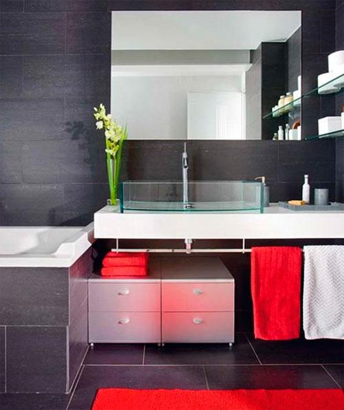 Красные полотенца в ванной комнате, оформленной в сером цвете, очень оживляют интерьер