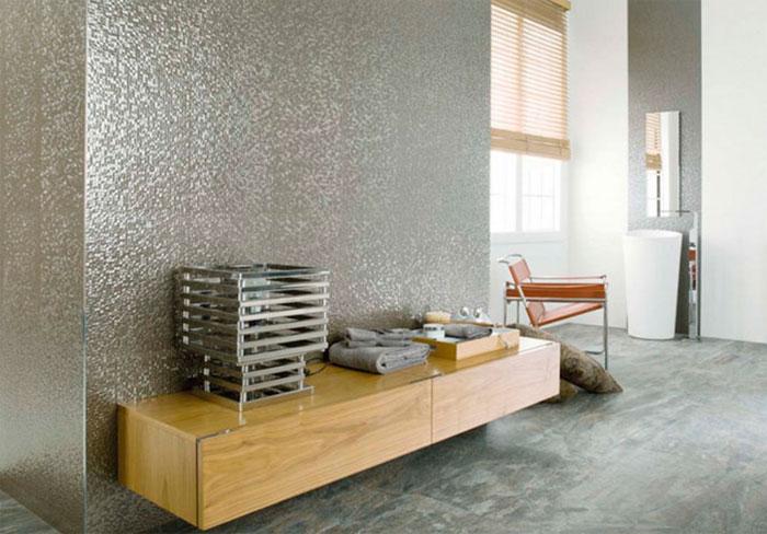 Керамическая плитка, как металл Керамическая плитка, имитирующая металл, появилась на рынке уже несколько лет назад. Сегодня она переживает возрождение популярности. На сегодняшний день, как и в предыдущий год, в моде керамические пластины, имитирующие дерево в основном коричневых оттенков или серых, которые подражают бетону. Дерево и бетон – это, по мнению экспертов, преобладающие тренды на 2016-2017 годы. Наряду с этим растущей популярностью пользуется керамика, имитирующая металл. Очень интересные варианты использования плитки, имитирующей металл можно найти в интерьере ванной комнаты в современном стиле. Они придадут искрящийся блеск ванной или суровости интерьеру в стиле лофт. Керамическая плитка, как металл, завоевала рынки несколько лет назад. Затем ее несколько забыли. Сегодня новые технологии позволяют достигнуть значительно более эффектных металлических эффектов, гораздо более интересных, чем это было раньше. Вот почему производители выпускают на рынок все больше и больше новых коллекций плитки под металл. Это может быть металлический кафель, имитирующий сталь, железо, медь, алюминий или хром и даже золото. Плитка под сталь может рассчитывать на внимание покупателей, предпочитающих стиль хай-тек или лофт, к которым она идеально подходит. Интересные варианты могут быть выбраны также для организации интерьера в стиле ретро и минималистических аранжировок. Варианты дизайна с керамической плиткой, как металл Представленная ниже плитка под сталь большого размера XXL представляет собой сборник итальянской керамики большого формата 300 x 150 см с изысканной и элегантной текстурой, имитирующей металлические поверхности. С ее использованием выполнена отделка просторных ванных комнат в стиле городской шик. Большие площади были дополнительно усилены характерной отделкой, подражающей коррозии металла и обогащенной модной белоснежной плиткой, деликатными украшениями в винтажном стиле, оформленными в металлические цвета. Очень часто «металлические» пластины предлагают в