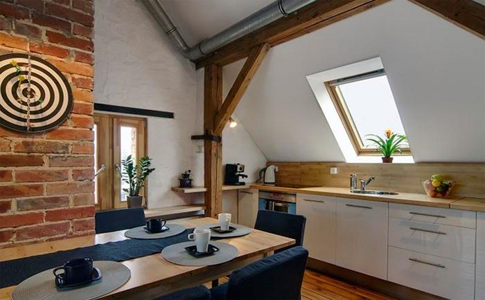 Белая кухня с деревянной столешницей и фартуком из деревянных панелей